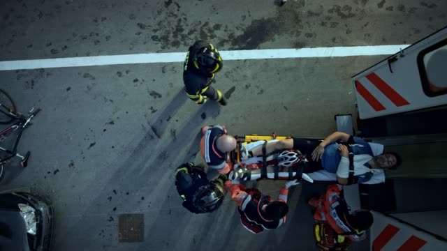 cs firefighters helping the paramedics load the injured cyclist into the ambulance - firefighter stock videos and b-roll footage