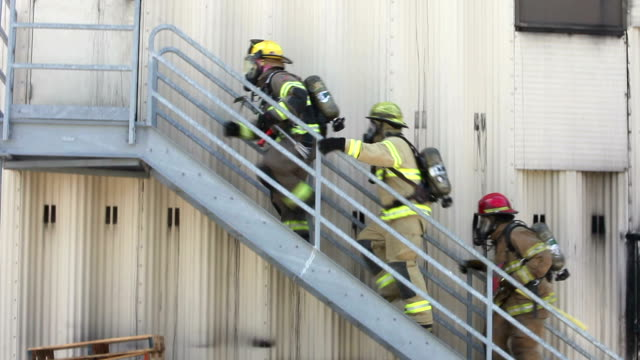 Firefighters in gear climbing stair to warehouse door video