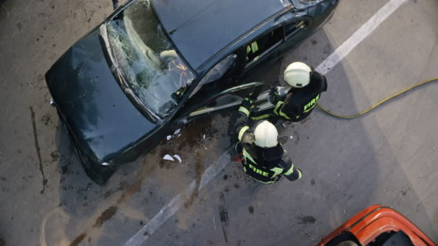 CS Firefighters opening the crashed car door with hydraulic spreaders Wide crane shot of firefighters opening the door of a crashed car with hydraulic spreaders at the scene of the accident. Shot in Slovenia. car accident stock videos & royalty-free footage