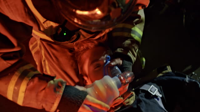 Firefighters placing a bag valve mask over the face of their fellow firefighter Medium handheld shot of firefighters placing a bag valve mask on the fellow firefighter and ventilating and oxygenating him near the fire scene at night. Shot in Slovenia. rescue worker stock videos & royalty-free footage