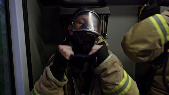 Firefighters placing the masks over their faces and communicating in the back of the fire truck heading to the scene of the fire video