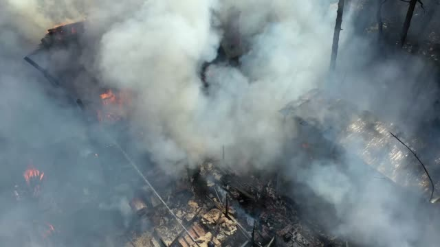firefighters pour water from fire hoses on the burning roof, smoke, protruding chimney. disaster fire. summer day. close-up from the drone . - tubo flessibile video stock e b–roll