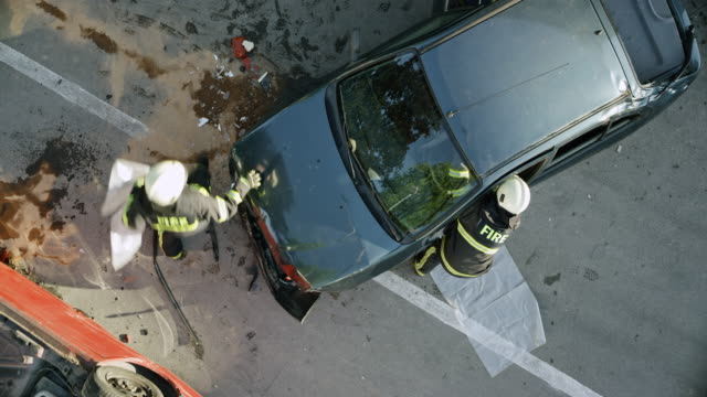 cs firefighters running to the people in a crashed car and saving them by cutting the roof off - incidente video stock e b–roll