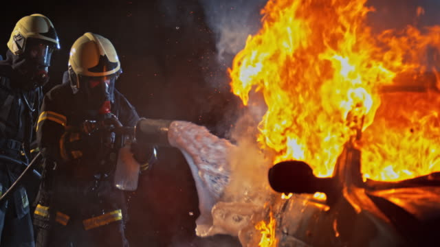 SLO MO Firefighters spraying foam onto a burning vehicle at night video