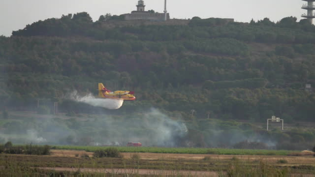 Firefighting aircraft Bombardier dump water on fire