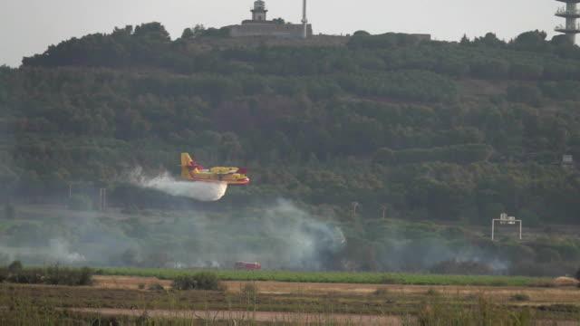 brandbekämpningsflygplan bombardier dumpar vatten i brand - släcka bildbanksvideor och videomaterial från bakom kulisserna
