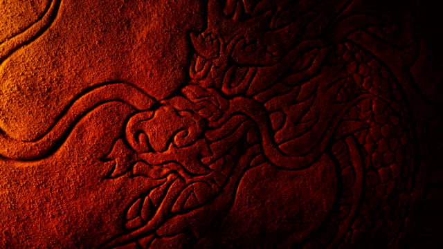 Firelight Flickers On Dragon Stone Carving Ancient carved stone art showing a traditional Chinese dragon creature ninja stock videos & royalty-free footage