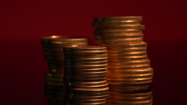 Firelight lighting effect on wide view of gold coins stacked with other piles in the background out of focus - video
