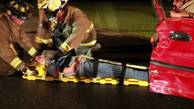 Fireman At Rescue Fireman help car crash victim. http://i286.photobucket.com/albums/ll113/jjneff/MedicalBanner.jpg stretcher stock videos & royalty-free footage