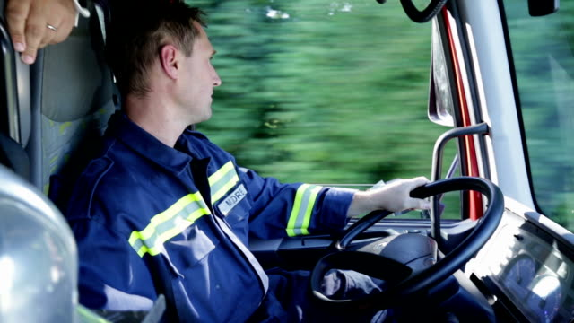 hd: fireman driving through the country in a firetruck - firefighter stock videos and b-roll footage