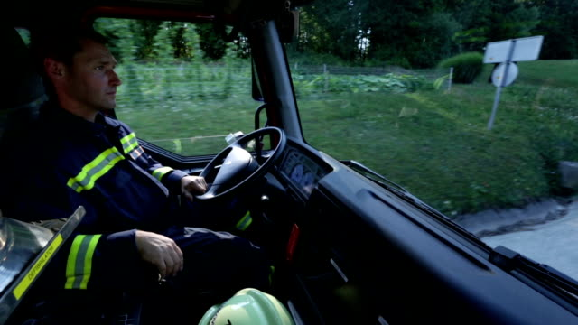 HD: Fireman in cabin driving a truck video