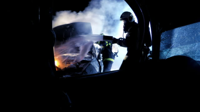 pov firemen extinguishing car fire with foam viewed from the other car involved in the accident at night - gommapiuma video stock e b–roll