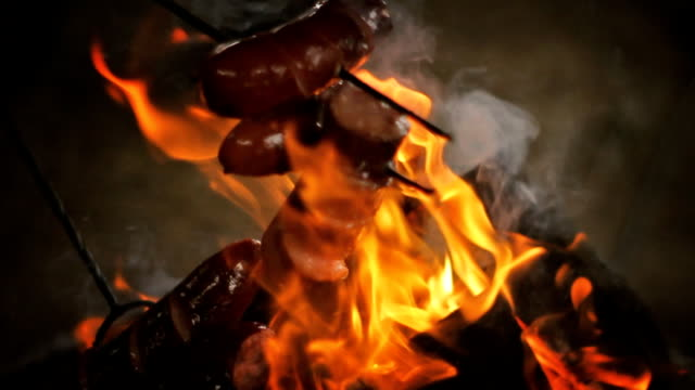 Fireplace and sausages. The fat melted. Evening. video