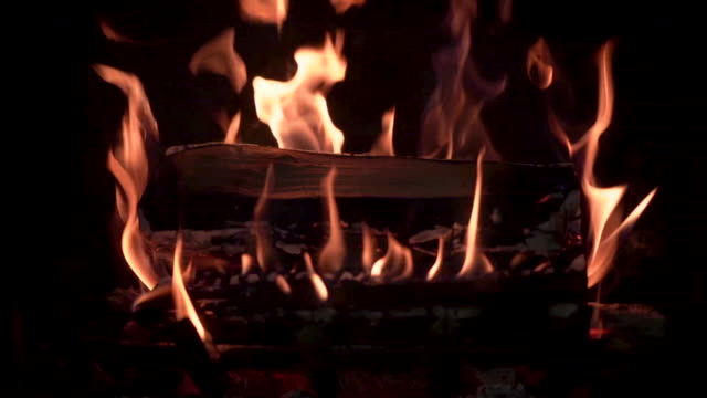 Fireplace burning with real wood A fireplace is burning intensely inside a wood fire stove. The clip is shot in slow motion. fireplace stock videos & royalty-free footage