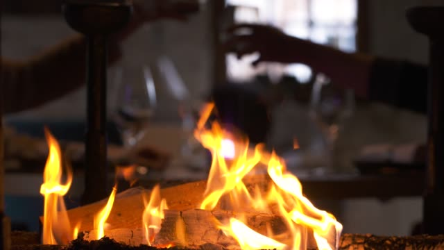 fireplace in a romantic restaurant, with a couple the background with a glass of champagne. we can see the couple cheering and being served by a waiter - close-up view - drinking and couple concept - happy hour video stock e b–roll