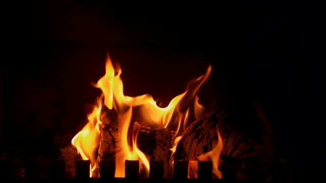 Fireplace Fireplace, slow motion. Light of the fire only. Seamless loop. fireplace stock videos & royalty-free footage