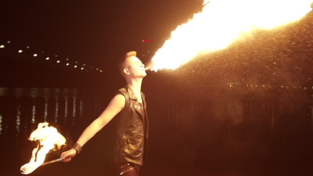 fireshow artist breathing fire by city riverside - трюк стоковые видео и кадры b-roll