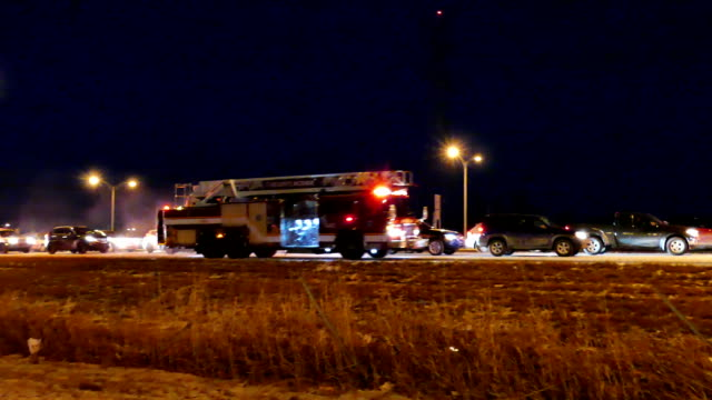 Firetrucks with lights and sirens arriving at scene of accident on highway video