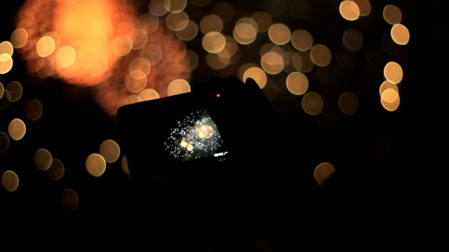 Firework and smartphone Someone is filming a firework with his tablet. fireworks videos stock videos & royalty-free footage