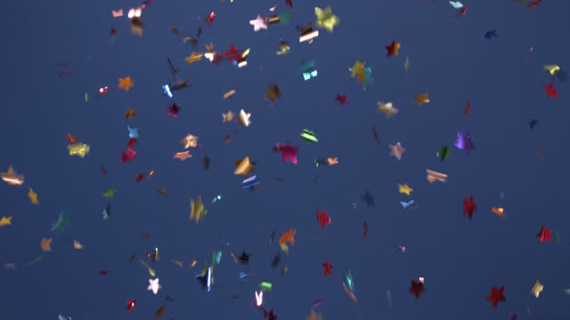 Fireworks from multi-colored flying confetti on a blue background for the holidays: birthday, Valentine's Day, New Year, Christmas, a solemn event. video