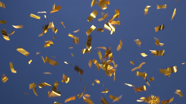 Fireworks made of golden confetti on blue background. video