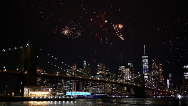 4k: фейерверк над бруклинским мостом в нью-йорке ночью - fireworks стоковые видео и кадры b-roll
