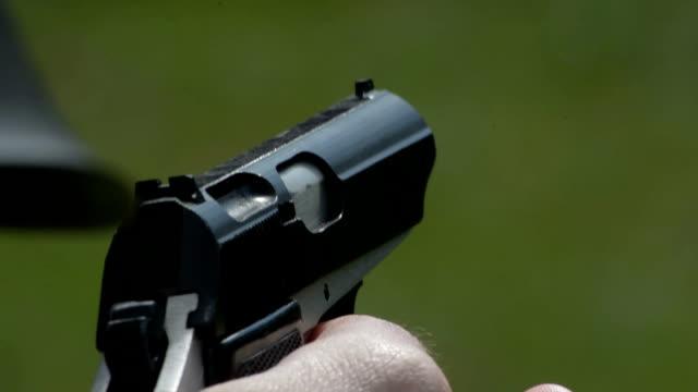 Firing pistol outside close up video