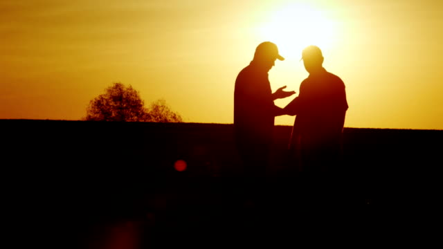 A firm handshake of two farmers on the field. They communicate, use a tablet. At sunset video