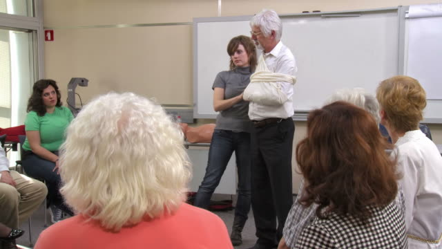 HD: First Aid Instructor Making An Arm Sling HD1080p: Young female instructor showing how to use a sling in case of arm injuries on a volunteer during first aid seminar for adults. orthopedic equipment stock videos & royalty-free footage