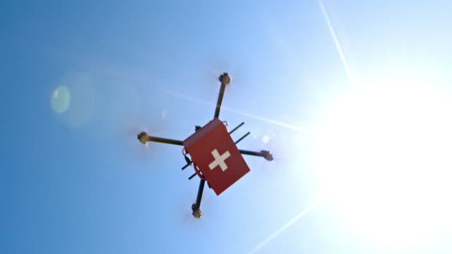 vídeos de stock e filmes b-roll de first aid kit carried across the sunny sky by a drone - resgate