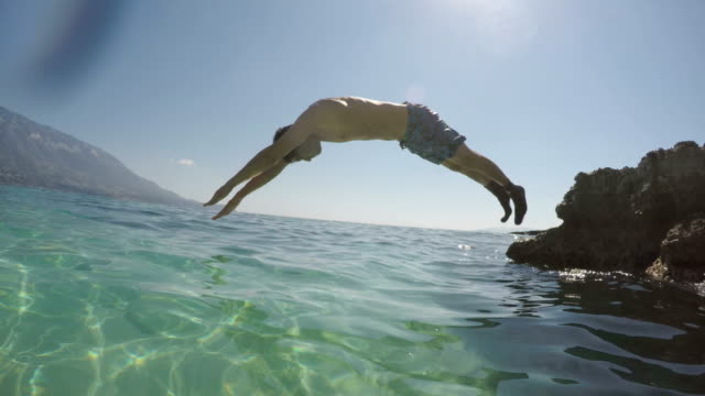 First class jump Young man with swimming goggles, socks and sneakers jumps from the cliff into the sea and dives. sock stock videos & royalty-free footage