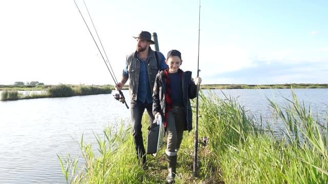 first fishing adult father and teen son - łowić ryby filmów i materiałów b-roll