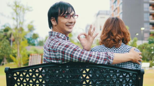 4 k : primo amore di coppia seduta in un parco - giuntura umana video stock e b–roll