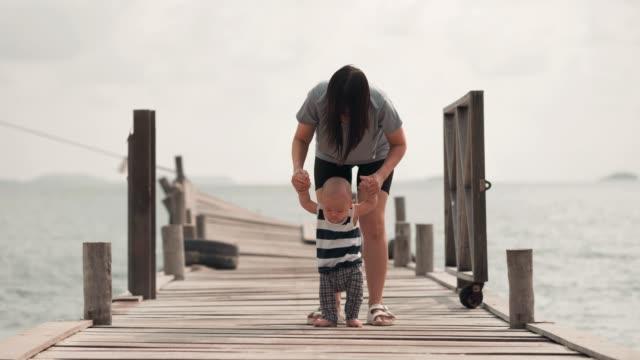Première occurrence : Jeune mère avec un enfant et premiers pas. - Vidéo