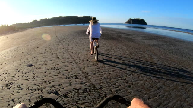 first person perspective as woman bicycles along tidal flat at sunrise - cestino video stock e b–roll