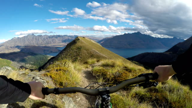 first person perspective of mountain biker descending hilly ridge line above iconic lake - percorso per bicicletta video stock e b–roll