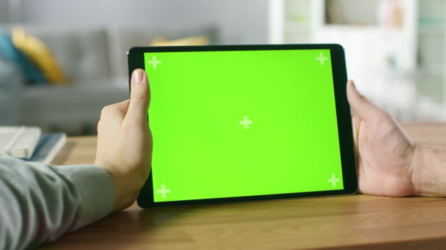 first person shot of a man using green mock-up screen digital tablet computer in landscape mode while sitting at his desk. in the background cozy living room. - tablet stock videos and b-roll footage