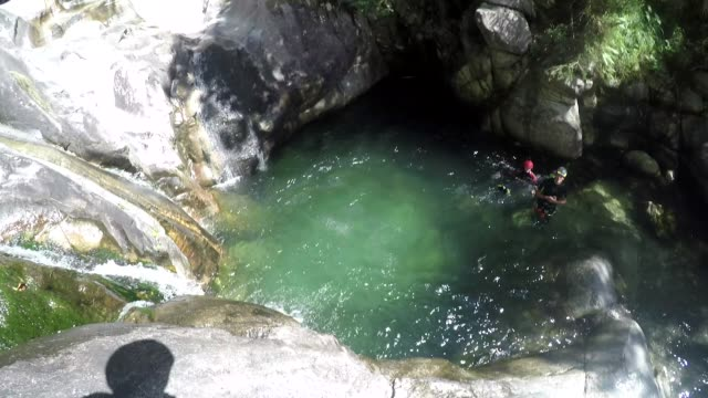 first person view canyoning, jumping off cliff into water - cliffs stock videos & royalty-free footage