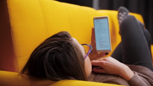 편안한 소파, 전자 담배 흡연 vaping에 누워 그녀의 스마트 휴대 전화를 사용 하 여 스크롤 여자의 첫 번째 사람이 볼 - 몸매 관심 스톡 비디오 및 b-롤 화면