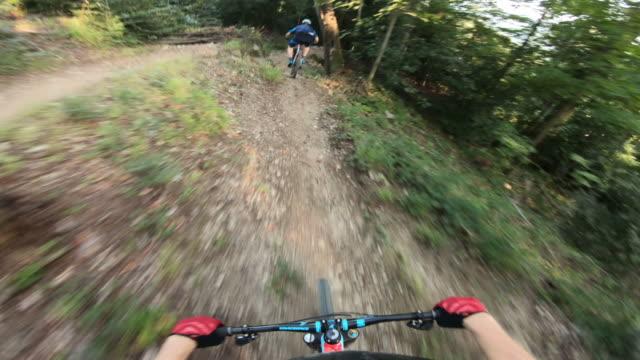 vista in prima persona dei mountain biker che scendono da un sentiero - percorso per bicicletta video stock e b–roll