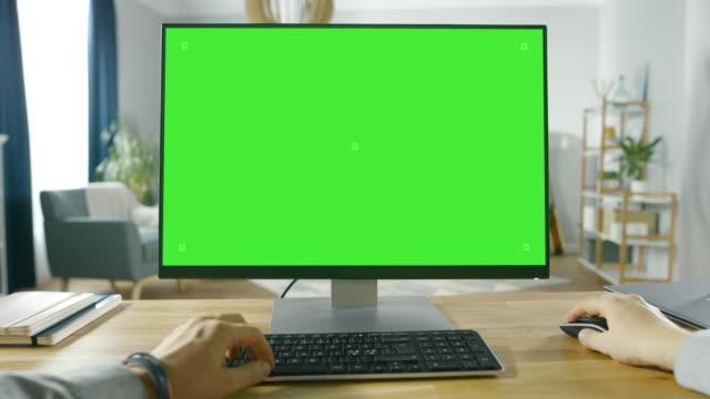 profesyonel freelancer yeşil mockup ekran kişisel bilgisayar evden çalışan ilk kişi görünümü. adam türleri, kullanan bilgisayarda rahat oturma odasını konforu, internet üzerinden tarama. - masaüstü bilgisayar stok videoları ve detay görüntü çekimi