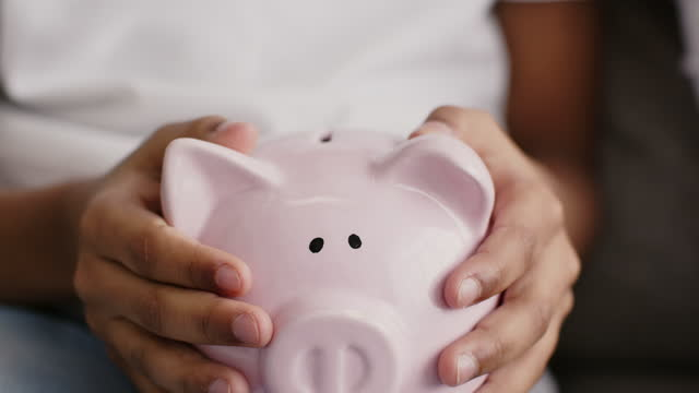 First savings. Close up of little girl putting coin into piggy bank, tracking shot, slow motion