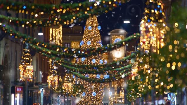 erster schneefall für die neujahrsferien. weiße schneeflocken wirbeln und fallen auf die straßen der stadt. weihnachts-europastadt mit weihnachtsbeleuchtung beleuchtet. - christmas decoration stock-videos und b-roll-filmmaterial