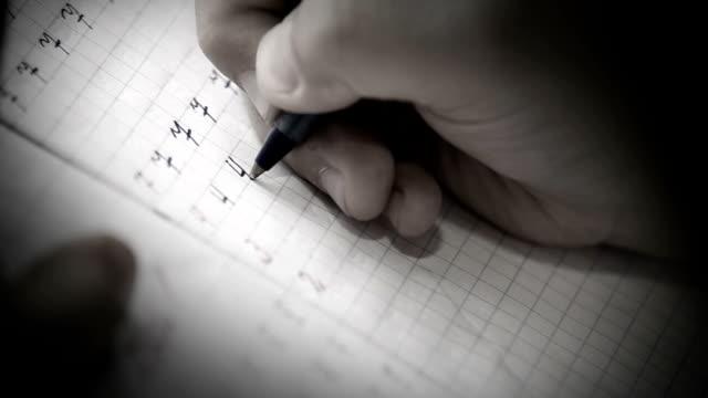 Primeiros passos por escrito: little aluno escrever dígitos na praça manual de grade - vídeo