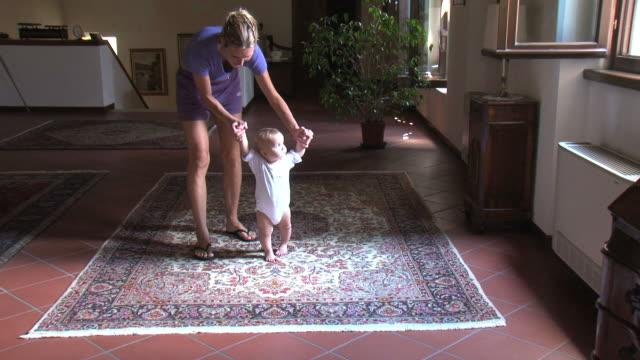 最初のステップのかわいい赤ちゃんの女の子 - 支えられた点の映像素材/bロール