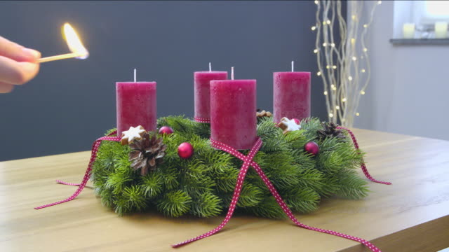 First Sunday of Advent - a young woman is lighting the first candle of the advent wreath video