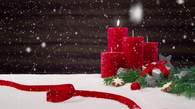 First Sunday of Advent - Beautiful snowfall in front of a Christmas decoration arrangement on a snowy table in front of a wooden background video