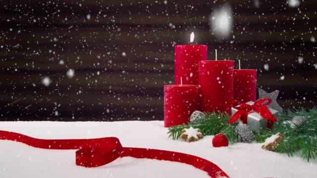 ersten sonntag im advent - schönen schneefall vor ein weihnachtsarrangement dekoration auf einem verschneiten tisch vor einem hölzernen hintergrund - advent stock-videos und b-roll-filmmaterial