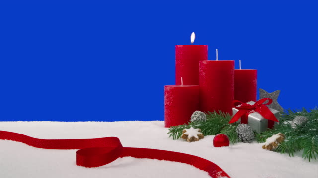First Sunday of Advent - Christmas decoration arrangement on a snowy table in front of a blue screen A Christmas decoration arrangement with four candles, fir branches, a wrapped gift, scattered decoration elements and a red ribbon on a snowy table in front of a blue screen. One candle is lit, which is burning with a beautiful flame. weihnachten stock videos & royalty-free footage