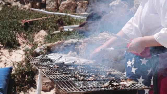 vídeos y material grabado en eventos de stock de pescado cocido en la parrilla al aire libre - pinzas utensilio para servir
